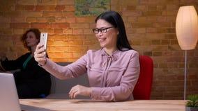 Tiro del primo piano della donna di affari asiatica adulta che ha una video chiamata sul telefono all'interno nell'ufficio Usando archivi video