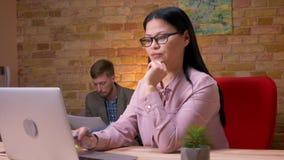 Tiro del primo piano della donna di affari asiatica adulta che lavora al computer portatile all'interno nell'ufficio Uomo d'affar video d archivio