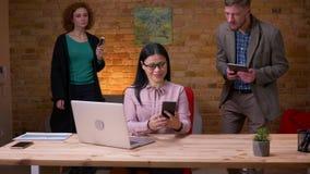 Tiro del primo piano della donna di affari asiatica adulta che lavora al computer portatile che riceve una notifica sul telefono  video d archivio