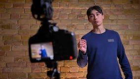 Tiro del primo piano della macchina fotografica che registra videoblogger maschio coreano che parla e poi che focalizza di nuovo  stock footage