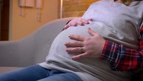 Tiro del primo piano della pancia di giovane femmina incinta che tiene delicatamente il suo stomaco mentre sedendosi sullo strato video d archivio