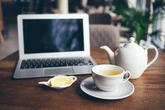 Tiro del primo piano della tazza di tè caldo con il limone e la teiera di infusione Immagini Stock Libere da Diritti