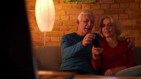 Tiro del primo piano delle coppie felici senior che guardano un documentario della TV sorridere allegramente sedendosi sullo stra archivi video