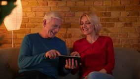 Tiro del primo piano delle coppie felici senior facendo uso della compressa che si siede sullo strato all'interno in un appartame archivi video