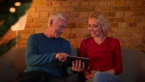 Tiro del primo piano delle coppie felici senior facendo uso della compressa e del sorridere allegramente sedendosi sullo strato a video d archivio