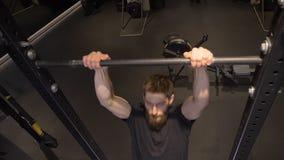 Tiro del primo piano di addestramento atletico muscolare adulto e di sollevamento del culturista sulle barre all'interno nella pa video d archivio