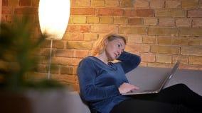 Tiro del primo piano di funzionamento femminile caucasico di eldery sul computer portatile e dell'essere seduta premurosa sullo s stock footage