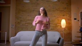 Tiro del primo piano di giovane ballare femminile caucasico castana grazioso e di divertiresi in un appartamento accogliente all' stock footage