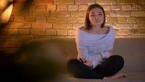 Tiro del primo piano di giovane bella femmina caucasica che guarda una manifestazione di TV e che è sensibile gridando seduta sul archivi video