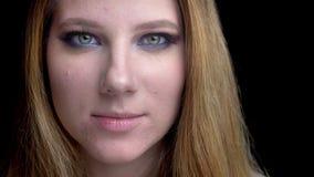 Tiro del primo piano di giovane bello fronte femminile con trucco sbalorditivo con fondo isolato sul nero video d archivio
