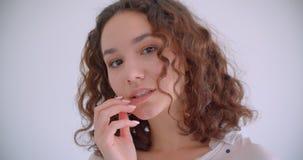 Tiro del primo piano di giovane bello sorridere femminile caucasico riccio felicemente riparando i suoi capelli che esaminano mac video d archivio