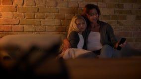 Tiro del primo piano di giovane caucasianmother e sua della figlia che guardano insieme una TV Abbracciare e coccole della mamma  archivi video