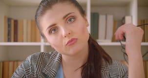 Tiro del primo piano di giovane donna di affari caucasica che esamina macchina fotografica che è alesata nell'ufficio delle bibli archivi video