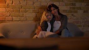 Tiro del primo piano di giovane donna caucasica e sua della bambina dolce che guardano una TV insieme abbracciare e sorridere video d archivio