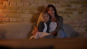 Tiro del primo piano di giovane donna caucasica e sua della bambina dolce che guardano una TV insieme abbracciare e sorridere Mam video d archivio