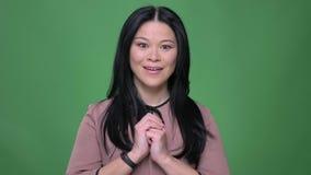 Tiro del primo piano di giovane femmina asiatica attraente con capelli neri che ottengono esame sorpreso ed eccitato diritto la m archivi video