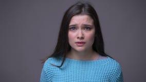 Tiro del primo piano di giovane femmina castana graziosa che è gridare triste esaminando macchina fotografica con fondo isolato s video d archivio