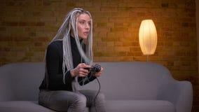Tiro del primo piano di giovane femmina caucasica attraente dei pantaloni a vita bassa che gioca i video giochi sulla TV e che vi archivi video