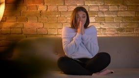 Tiro del primo piano di giovane femmina caucasica che guarda un film horror su una TV e che ottiene spaventata coprendo il suo fr stock footage