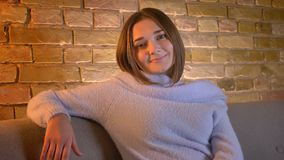 Tiro del primo piano di giovane femmina caucasica che sorride e che osserva diritto la seduta della macchina fotografica rilassat video d archivio