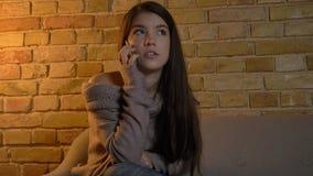 Tiro del primo piano di giovane femmina caucasica graziosa che ha una conversazione casuale sul telefono mentre riposando sullo s immagine stock