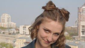 Tiro del primo piano di giovane femmina caucasica graziosa che sorride e che posa felicemente davanti alla macchina fotografica c stock footage