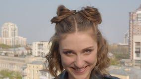 Tiro del primo piano di giovane femmina caucasica graziosa che sorride e che posa felicemente davanti alla macchina fotografica c archivi video