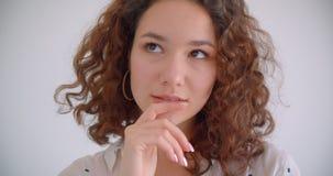 Tiro del primo piano di giovane femmina caucasica riccia dai capelli lunghi graziosa che è sorridere premuroso felicemente esamin video d archivio