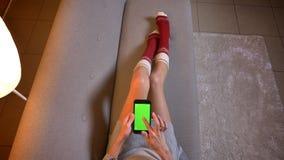 Tiro del primo piano di giovane femmina che guarda un film sul telefono con lo schermo verde di intensità Le coscie della donna n immagini stock libere da diritti
