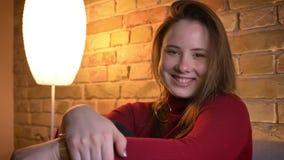 Tiro del primo piano di giovane femmina grassottella affascinante che esamina macchina fotografica e che sorride in un appartamen archivi video