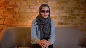 Tiro del primo piano di giovane femmina musulmana attraente nel hijab che guarda un film 3D sulla TV e che ottiene un jumpscare m archivi video