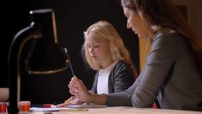 Tiro del primo piano di giovane madre caucasica che aiuta la sua piccola figlia dolce con fondo isolato sul nero archivi video
