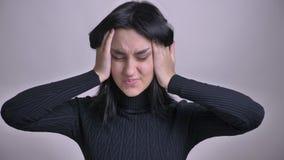 Tiro del primo piano di giovane overthinking femminile caucasico grazioso e di ottenere un'emicrania davanti alla macchina fotogr video d archivio
