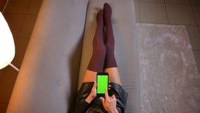 Tiro del primo piano di giovane scorrimento femminile adolescente sveglio sul telefono con lo schermo verde di intensità Coscie d immagine stock libera da diritti