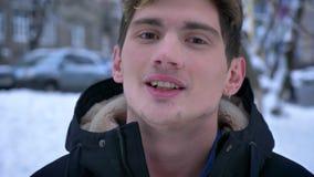 Tiro del primo piano di giovane sogno caucasico attraente e di sorridere mentre esaminando macchina fotografica all'aperto in un  video d archivio