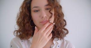 Tiro del primo piano di giovane sorridere femminile caucasico riccio dai capelli lunghi grazioso macchina fotografica felicemente archivi video