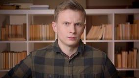 Tiro del primo piano di giovane studente maschio caucasico attraente che ondeggia la sua testa che non dice essere arrabbiato esa video d archivio