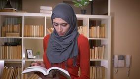 Tiro del primo piano di giovane studentessa musulmana attraente nel hijab che legge un libro all'interno nell'università delle bi video d archivio