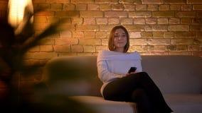 Tiro del primo piano di giovane TV di sorveglianza femminile caucasica e di risata mentre sedendosi sullo strato all'interno stock footage