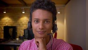 Tiro del primo piano di giovane uomo d'affari indiano in cuffie che esaminano macchina fotografica che sorride happilly nell'uffi archivi video
