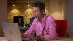 Tiro del primo piano di giovane uomo d'affari indiano in cuffie che scrive sul computer portatile nell'ufficio all'interno stock footage