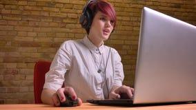 Tiro del primo piano di giovane videoblogger femminile adolescente grazioso nel flusso continuo delle cuffie in tensione mentre f fotografia stock libera da diritti