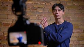 Tiro del primo piano di giovane videoblogger maschio coreano che parla e che è registrato sulla macchina fotografica stock footage