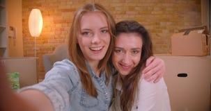 Tiro del primo piano di giovani bei blogger lesbici delle coppie che parlano sulla macchina fotografica che scorre abbracciare in archivi video