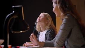 Tiro del primo piano di piccola ragazza bionda graziosa che risponde alla sua domanda algebrica delle madri con fondo isolato sul video d archivio