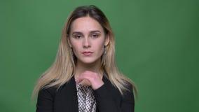 Tiro del primo piano di sguardo femminile caucasico dei giovani pantaloni a vita bassa attraenti diritto e di posa davanti alla m video d archivio