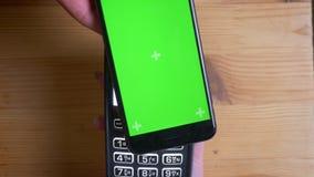 Tiro del primo piano di un terminale di pagamento che è usato per il pagamento da una pubblicità sul telefono con lo schermo verd archivi video