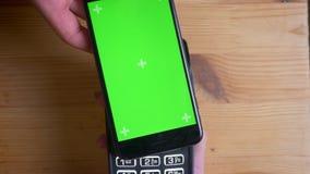 Tiro del primo piano di un terminale di pagamento che è usato per il pagamento da una pubblicità sul telefono con lo schermo verd stock footage