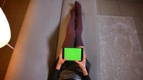 Tiro del primo piano del influencer sociale femminile di media che manda un sms sulla compressa con lo schermo verde di intensità immagini stock libere da diritti