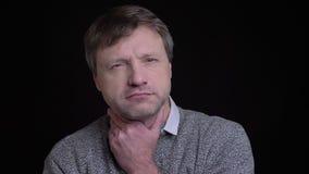 Tiro del primo piano del maschio caucasico adulto che ha una gola malata e che è malato davanti alla macchina fotografica video d archivio
